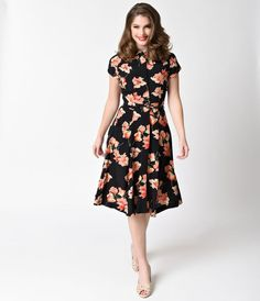 Polly is an enchanting 1930s inspired floral frock with an elegant high neckline, a dainty Peter Pan collar, and cap sleeves, complete in a breathtaking pink floral print set against a ravishing black background. The hidden button up style is lined on the