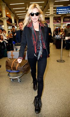 Kate Moss wears a black t-shirt, printed collared shirt, silk scarf, black skinny jeans, a blazer, black sunglasses, and fringe boots