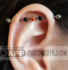 Healed industrial piercing with 3mm prong set tangerine CZ with two 3mm prong set onyx gems. Jewelry from Anatometal.