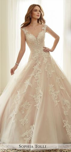 Misty tulle ball gown with illusion slight cap sleeves adorned in generously hand-beaded lace appliqués and scattered beading, deep V-neckline with partially concealed sheer peekaboo, lightly beaded lace appliqués adorn bodice and spill down voluminously folded skirt, back corset, chapel length train.