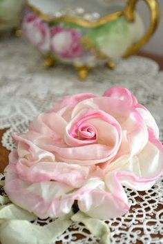 Beautiful ribbon work. Looks like silk, tinted on the edges of the 'petals'.  love the tatted doily