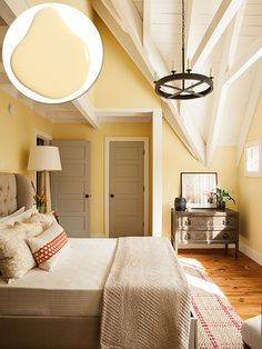 Tucked under the front gable, the upstairs master bedroom gains height—and interest—by exposing the structure overhead, all rough-sawn white pine painted in Olympic® Paint's Crumb Cookie with walls in Cornmeal. Showing off beams and rafters throughout the cottage lends a lofty feel. Photo: Deborah Whitlaw Llewellyn