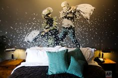 "A Banksy wall painting showing Israeli border policeman and Palestinian in a pillow fight is seen in one of the rooms of the ""The Walled Off Hotel"" in the West Bank city of Bethlehem, Friday, March 3, 2017. The owner of a guest house packed with the elusive artist Banksy's work has opened the doors of his West Bank establishments to media, showcasing its unique ""worst view in the world."" The nine-room hotel named ""The Walled Off Hotel"" will officially open on March 11. (AP Photo/Dusan…"
