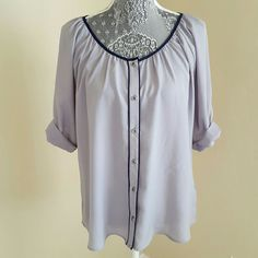 Express Button Up Blouse Great for work or a night out, this top features 3/4 sleeves with roll tab, pleated neckline, sliver tone buttons, semi-sheer light gray bodice with navy blue piping detail. Pre-loved and in excellent condition. 100% polyester, machine washable. Express Tops Blouses