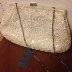 Santi White Eyelet Evening Clutch This white eyelet Santi bag can be held as a clutch or worn as a short shoulder bag. It has been pre-used and there are some signs of wear in slight discoloration (shown in photos). Comes with original dust bag.  ✔️15% off bundles ✔️Smoke-free Home ✖️PayPal (it protects us both!) ✖️Trades Santi Bags Clutches & Wristlets