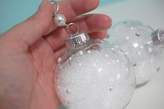 clear glass Christmas ornament filled with snow and decorated with pearls
