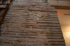 Crumbling plaster between strips of lathe