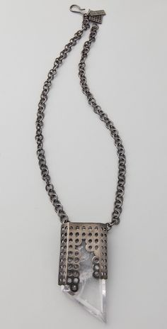 Gunmetal plated chain necklace featuring a quartz crystal encased in perforated metal. By Kelly Wearstler.