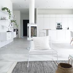 Valoisa valkoinen valtaa sisustuksen. Olohuone, ruokailutila ja keittiö yhdistyvät kauniiksi kokonaisuudeksi. Kokonaisuuden kruunaa upea valkoinen takka tilan keskellä.