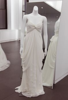 Brides: White by Vera Wang - Fall 2012. Sleeveless chiffon sheath wedding dress with a ruched v-neckline and floral details on the layered skirt, White by Vera Wang