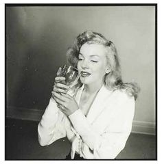 """Marilyn Monroe enjoying a drink in a photo by Philippe Halsman for an October 10, 1949 LIFE Magazine article called """"Eight Girls Try Out Mixed Emotions"""" by Dr. Robert Oppenheimer. The eight girls- Lois Maxwell, Suzanne Dalbert, Ricky Soma, Laurette Luez, Jane Nigh, Dolores Gardner, Marilyn Monroe, and Cathy Downs."""