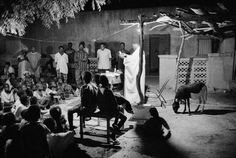 MALI. Village of Bandiagara. 1996. Abbot Georges FONGORO celebrates an evening mass inside a parishioner's courtyard. Magnum Photos Photographer Portfolio