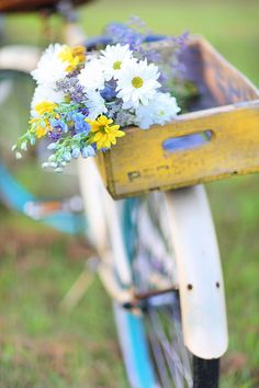 Bouquet of country flowers in a vintage yellow crate on a lovely vintage bike. So sweet