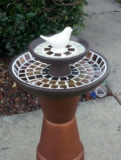 How to make a terra cotta pot birdbath with bright colors inspired by MacKenzie Childs. Mask and spray paint the pots then stack to make a bright bird bath.A Terra Cotta Pot Birdbath is the perfect way to reuse old pots while also making something new and