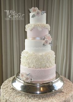This romantic blush wedding cake has layers of lace & ruffles with sugar paste flowers. By www.WhoMadeTheCake.com #BlushWeddingCake #RuffleWeddingCake #Floralweddingcake #weddingcake