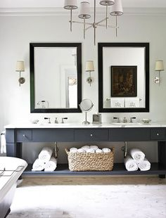 dark console & twin framed mirrors w/sconces and amazing chandelier