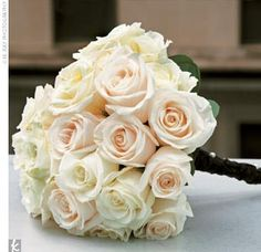 Heather held a clutch-style bouquet of cream roses tightly wrapped in black ribbon.  from the album: Heather & Andrae: A Modern Wedding in Charlotte, NC