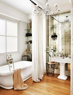 Glamorous bathroom-distressed mirror, beaded chandelier, and floor to ceiling curtain