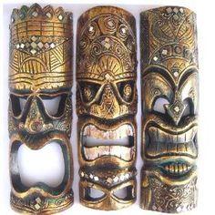 three intricately carved wood tiki masks