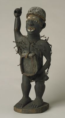 Wooden nail-covered figure of a man with a box on his stomach