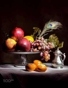 Autumn fruits: pomegranates, red grapes, persimmons, and a peacock feather arranged on a glass pedestal over a white mat covered table, and a small silver pitcher on the right