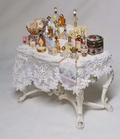 VICTORIAN STYLE PERFUMERIE TABLE No. #9:  This is a Jiayi hand carved wooden table finished in Ivory cream with gold antiquing. All the little bottles are designed by me and are solid...On one side at the back is an enamel hinged box and the other side has a golden bowl filled with boxes..Genuine antique lace is used to give this piece a feminine elegance. The boxes are designed by Susan Harmon.