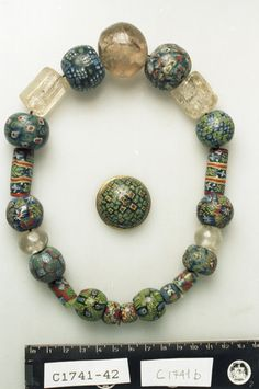 17 beads of glass. Mosaic Beads. Buckle of bronze. Photo Documentation in connection with loans of objects to Nautical Museum, Rørvikneset, Nord-Trøndelag.  Norway, Nord-Trøndelag, VIKNA, Ryum.