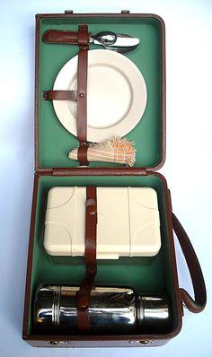 """Valigetta portavivande degli anni '70. Era un gadget offerto dalle stazioni di servizio Esso per fidelizzare i propri clienti. Rivestita di similpelle e tela, dotata di doppia chiusura a scatto con chiavi, la valigetta racchiude un thermos, una scatola per alimenti, un tovagliolo, due piatti e quattro posate. Il marchio """"Esso"""" è stampato sul cinturino di fissaggio dei piatti."""