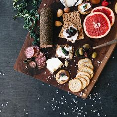 Stunning food photography for Zest, Lititz, PA. Bold, bright, savory. Fruit, cheese, meat, crackers, olives, nuts on wood and slate background.