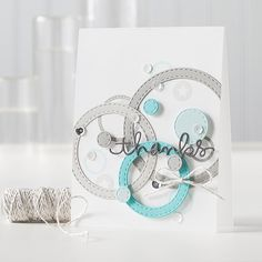 Stitched circle and ring die cuts in shades of smoke and blue look like they are floating on this handmade thank you card.  Use pop-up foam on some of them to enhance the illusion.  Add sequins!