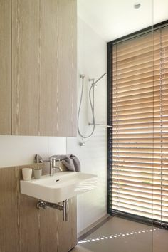 Lamble Residence / Smart Design Studio. Pinned by Karen Johnson Landscape Design. tapware, sink, large white tiles, timber detail, timber exterior blinds