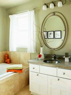 Inexpensive elegance - A concrete countertop dresses up basic white-painted cabinetry and looks great with brushed-nickel fixtures and accessories. Black-and-white photography, opposite the mirror, is easy art. Bargain white fabric makes pretty drapes.