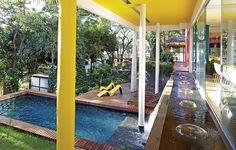 O arquiteto Leo Romano manteve as árvores no terreno em declive e projetou o paisagismo com plantas tropicais e espelho-d'água com queda para a piscina. Assim, as áreas internas e externas parecem se confundir