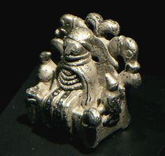 Odin from Lejre, Denmark - a small cast silver figurine from c. 900 CE, depicting an individual on a throne wearing a floor-length dress, an apron, four bead necklaces, a neck ring, a cloak and a rim-less hat. Two birds are seated on the armrests and the back of the throne features the heads of two animals. (wiki)