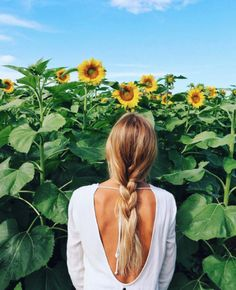 Olive Cooke stopping to smell the sunflowers in our Open Horizons Dress.