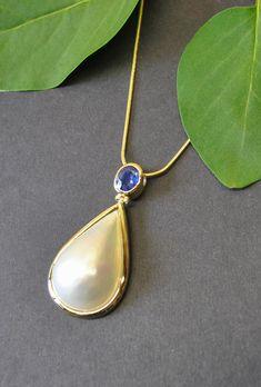 Dieser wunderschöne Unikatanhänger ist handgefertigt aus 14 kt Gold. Er überzeugt mit seiner schlichten Eleganz durch eine tropfenförmige Mabe Perle an einem tiefblauen Saphier mit stolzen 0,82 ct. Die Mabe Perle ist eine halbkugelförmige Perle, die an der Schaleninnenseite von Austern wächst. Kugel, Pendant Necklace, Gold, Jewelry, Sapphire, Gems, Pearls, Deep Blue, Oysters