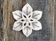 Handmade snowflake using felt, yarn & beads...pretty cute! This would make adorable Christmas tree ornaments or even cute on a gift box.