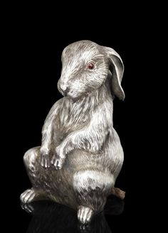 A jewelled silver bell-push Fabergé with Imperial Warrant, Moscow, 1899-1908 a realistically cast and chased figure of a rabbit standing alert on hind legs, with garnet pushpiece eyes, 84 standard height: 11.2cm (4 3/8 in).