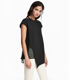 Black. Top in woven viscose fabric with a round neck and cut-out sections at neckline. Cap sleeves, sheer section at one side, and asymmetric hem. Longer at