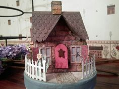 Tim Holtz Village Dwelling on a round decorated box with an acorn cap for a flower box on side windows and a rusted star on the door.