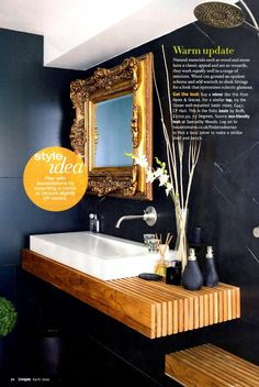 Dark bathroom walls with a gold mirror and warm wood counter