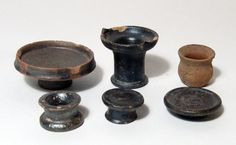 Campanian ceramic votive vessels, 4th century B.C. South Italian pottery miniature votive vessels, bowls, shallow bowl and kalathos, five with black slip gloss, each miniature for use as an offering, shallow bowl largest 2.5 cm high and 6.4 cm diameter. Private collection