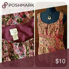 """Pretty Sleeveless Top Very pretty dressy floral print sleeveless top in various shades of plum and lavender with cream and light blue. Gathered front bust with ribon trim underneath and bow at front left.  Bust measures 20.5"""" across. 100% polyester. Very good used condition. Tops"""