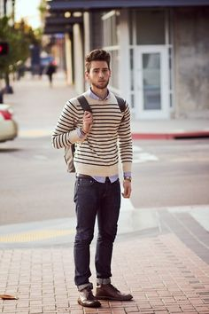 Casual sweater and collared shirt combo with brown shoes and blue jeans.