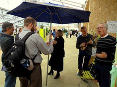 """Episcopal Bishop Marc Andrus leads one of several """"pop up"""" worship services in the """"green zone"""" for COP21 visitors. The purple umbrella is a way of notifying folks of the gathering within the very busy """"green zone."""" Photo by Brian Kaylor. See a video interview with Andrus about these gatherings here: vimeo.com/147898994"""