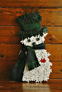 This little snowman made from repurposed puzzle pieces is so cute that he deserves a pin...even if to wait for next year! SO many puzzles available at thrift stores...waiting for a new life like this.