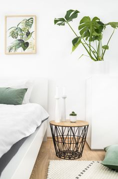 Greenery in the bedroom with matching pillows, plants and art