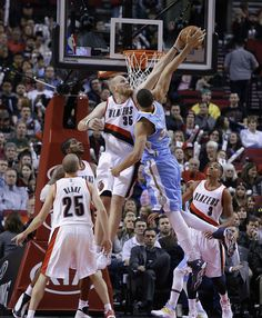 Description of . Portland Trail Blazers center Chris Kaman (35) blocks a shot by Denver Nuggets center JaVale McGee during the second half of an NBA basketball game in Portland, Ore., Sunday, Nov. 9, 2014.  Portland won 116-100.(AP Photo/Don Ryan)
