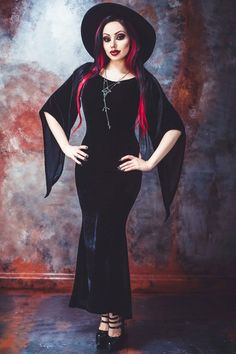 Freya Maxi Dress by Necessary Evil is made from a black stretch velvet material. The Gothic Dress has a flattering boat neck cut, wide bell sleeves, a slightly curve-hugging shape and fishtail hem.