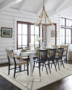 Black wooden chairs in a light dining room with a natural chandelier - Serena & Lily